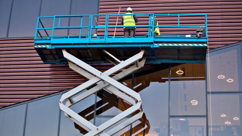 Builder on a Scissor Lift Platform at a construction site. Men at work