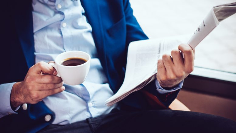 Young businessman in a blue jacket with a cup of coffee, reading a newspaper in a cafe
